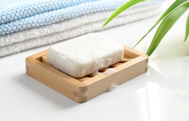 나무 비누 접시에 거품이 있는 흰색 비누 바, 흰색 테이블에 면 수건.