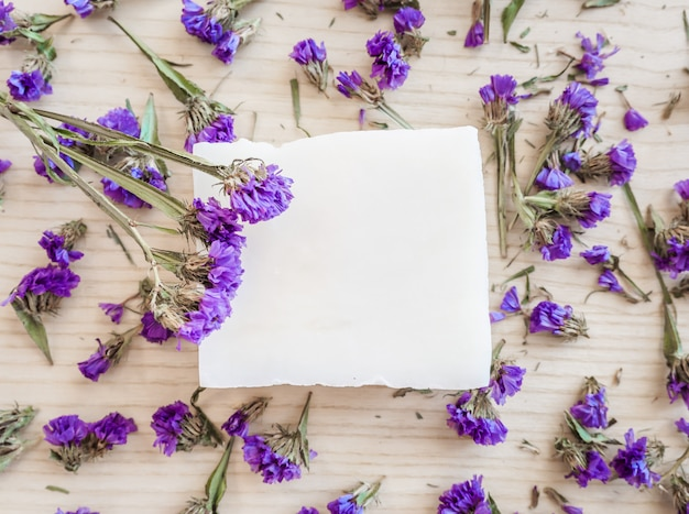 White soap bar on a wooden background with violet followers top view