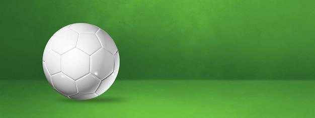 緑のスタジオバナーに分離された白いサッカーボール。 3dイラスト