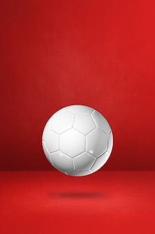 White soccer ball isolated on a red studio background. 3d illustration