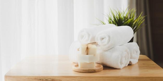 Белые мягкие сложенные полотенца и органическое мыло на деревянном столе с размытым белым фоном ванной