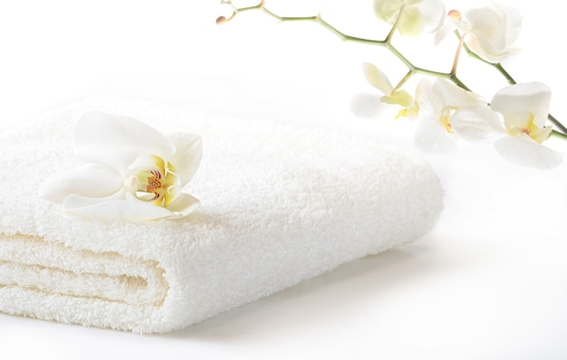 흰 난초 지점과 흰색 배경에 꽃과 흰색 부드러운 수건