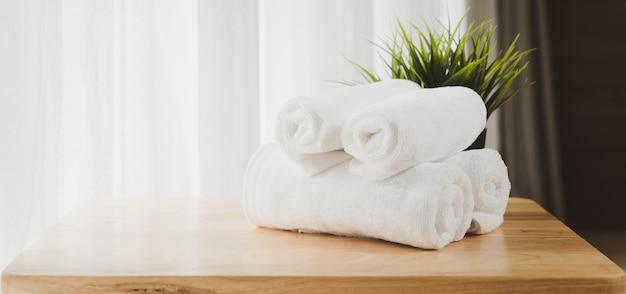 Белые мягкие полотенца, сложенные на деревянном столе с размытым белым фоном ванной комнаты