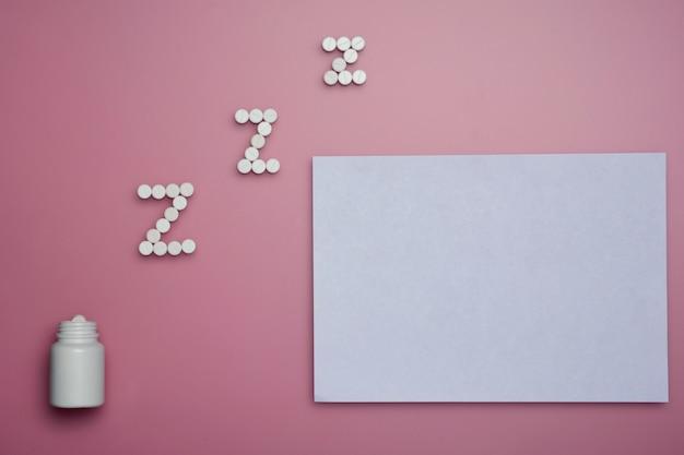 Белые somnifacient таблетки для z письмо и чистый лист бумаги на розовом фоне. копировать пространство