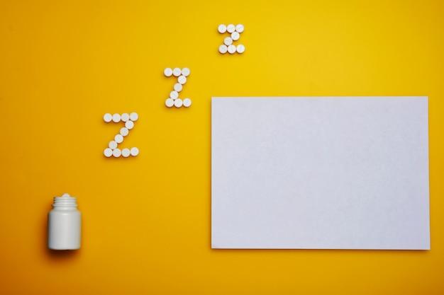 Белые somnifacient таблетки для z письмо и чистый лист бумаги на желтом фоне. копировать пространство