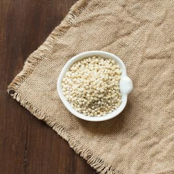 黄麻布のボウルに白いソルガムの穀物
