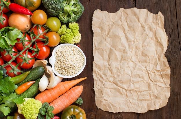 Зерна белого сорго в миске с овощами и крафт-бумагой по дереву