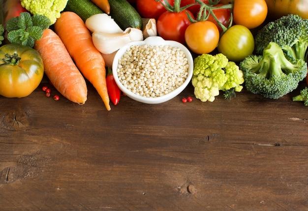 木製のテーブルに野菜と白いソルガムの穀物