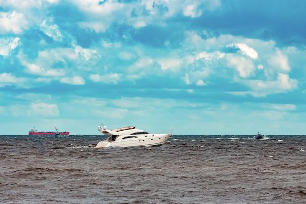 Белый скоростной катер быстро движется к балтийскому морю. водные виды спорта