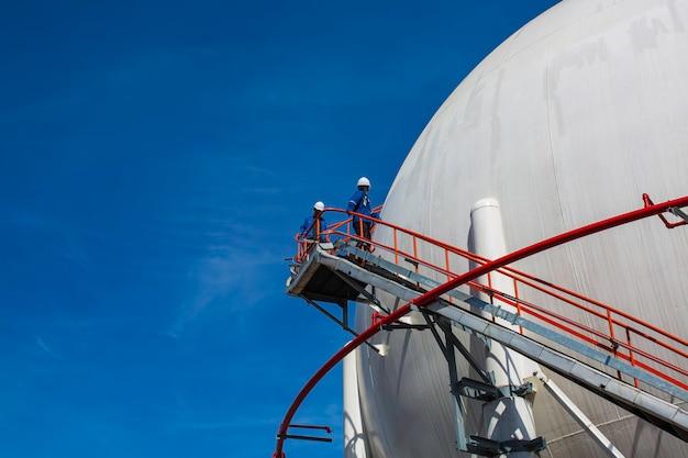 Белые сферические пропановые баки, содержащие трубопровод топливного газа и строительные леса