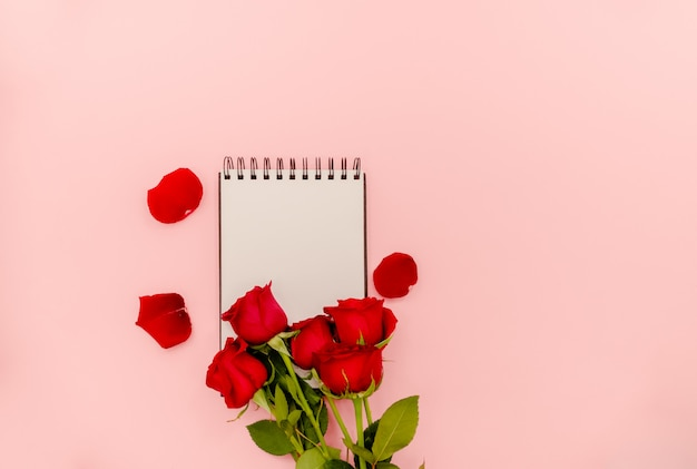 White spiral notepad with red roses on light pink background.