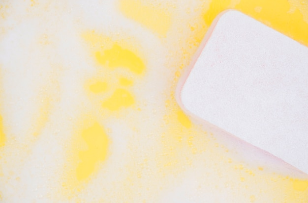 White sponge floating on soap sud over yellow background