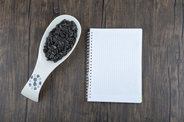 White spoon full of healthy black sunflower seeds placed on a wooden table .