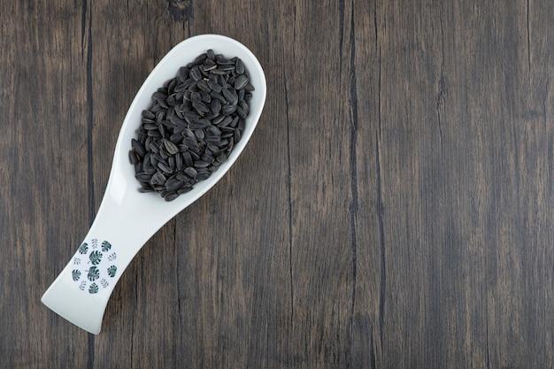 건강 한 검은 해바라기 씨앗이 가득한 흰색 숟가락은 나무 테이블에 배치됩니다.