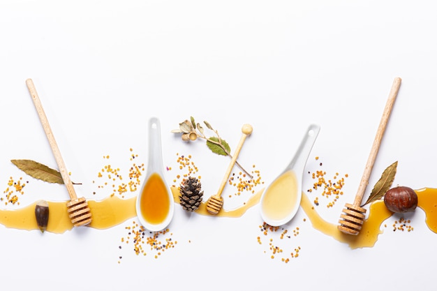 White spoons and honey sticks, with spilled honey
