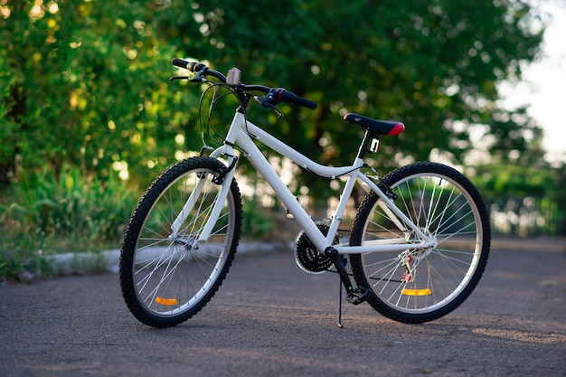 White sports bike with 16 speeds without logos on a background of green trees
