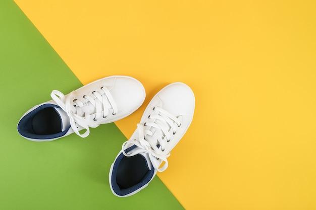 Белые спортивные туфли, кроссовки с шнурки на зеленом и желтом фоне. концепция спортивного образа жизни