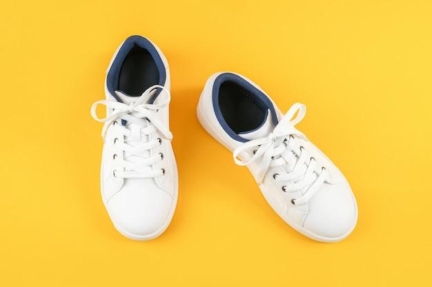 Белые спортивные туфли, кроссовки с шнурки на желтом фоне. концепция спортивного образа жизни вид сверху flat lay