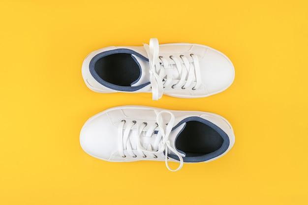 흰색 스포츠 신발, 노란색 배경에 구두 끈이있는 운동화. 스포츠 라이프 스타일 컨셉