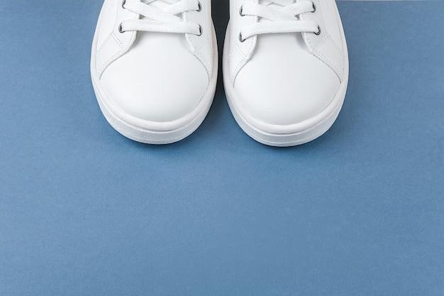 흰색 스포츠 신발, 파란색 배경에 구두 끈과 운동 화. 스포츠 라이프 스타일 개념 상위 뷰 평면 누워 복사 공간.