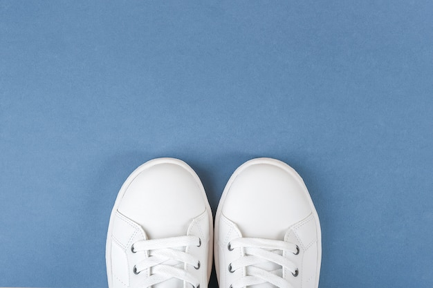白いスポーツシューズ、青の靴ひも付きスニーカー