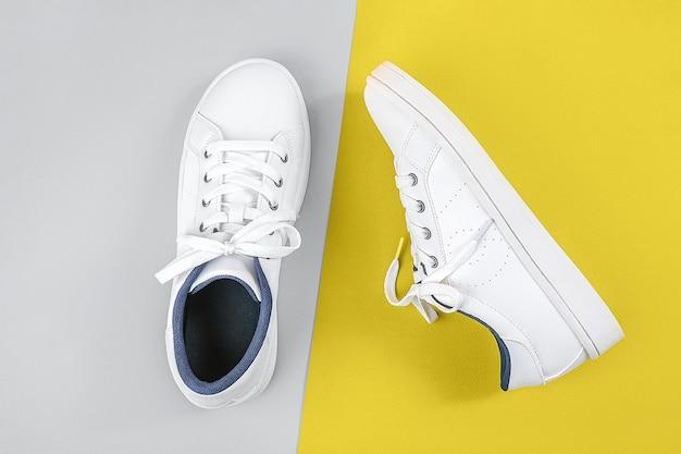 白いスポーツシューズ、黄色とグレーの靴ひもが付いたスニーカー