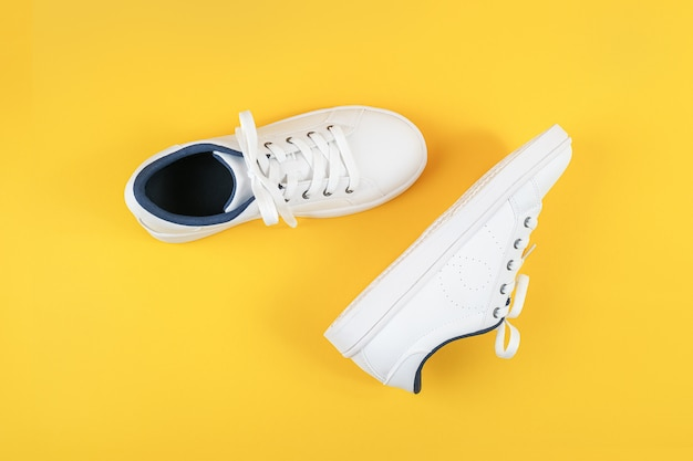 White sports shoes, sneakers with shoelaces on a yellow background. sport lifestyle concept top view flat lay