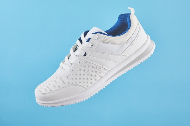 흰색 스포츠 스니커즈는 파란색 배경에 뜨고 있습니다. 피트니스를위한 세련된 남자 운동화.