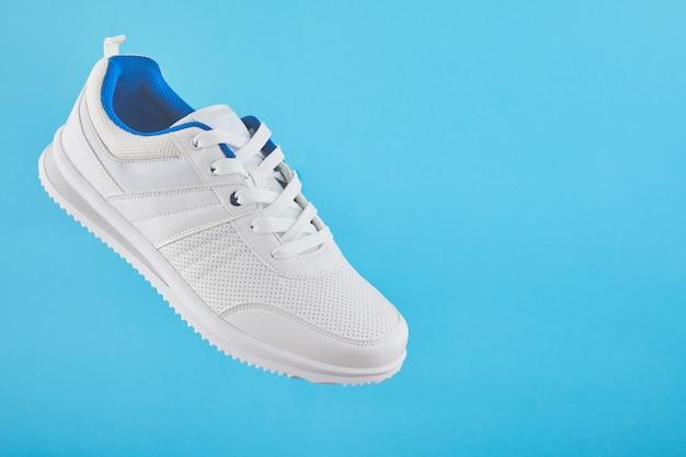 Белые спортивные кроссовки левитируют на синем фоне. стильные мужские кроссовки для фитнеса.