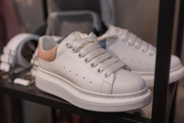 Белые спортивные кроссовки на полке в обувном магазине.