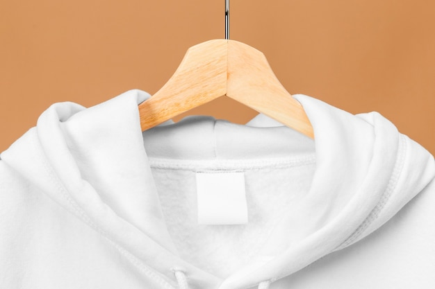 White sports sweatshirt with clothing tag on wooden hanger