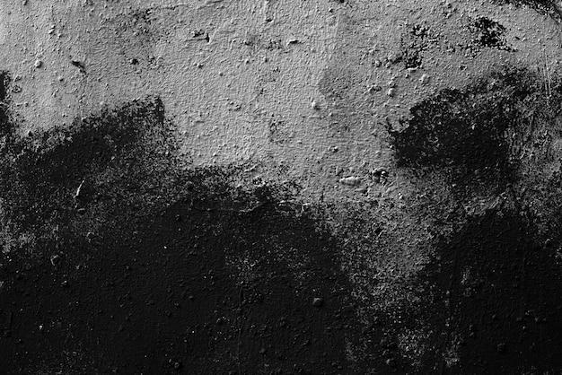 Белые пятна краски на черной поверхности штукатурки. абстрактный черный фон. черная текстура темная шероховатая поверхность.