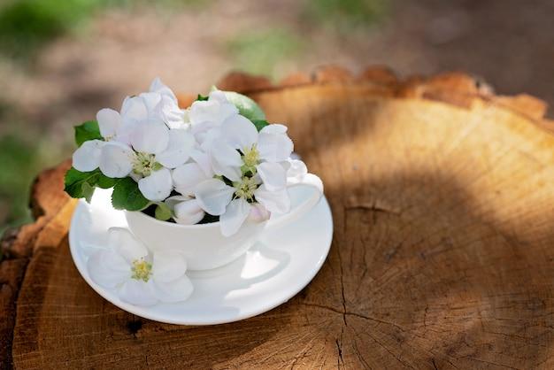 白い春のリンゴの花は、自然な木製の背景のコーヒーカップに花が咲きます。春夏のコンセプトです。コピースペース。