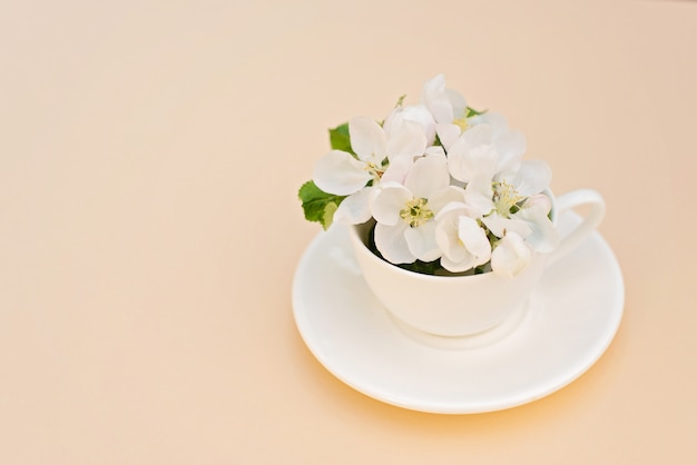 White spring apple tree blooming flowers in a coffee cup on a beige background. spring summer concept. greeting card. copy space.