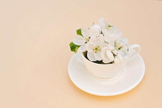 ベージュ色の背景のコーヒーカップに花が咲く白い春のリンゴの木。春夏のコンセプトです。グリーティングカード。コピースペース。