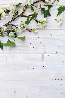 白い春の花と木製のテーブルの葉