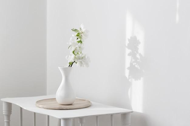 ヴィンテージの棚の上に花瓶の白い春の花
