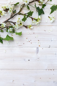 White spring flowers and leaves on a wooden table
