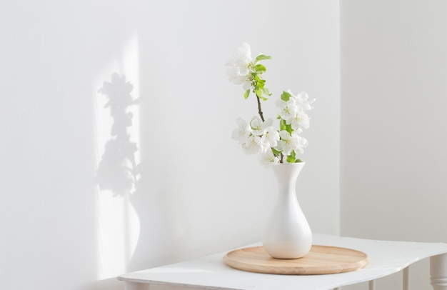 White spring flowers in vase on vintage shelf