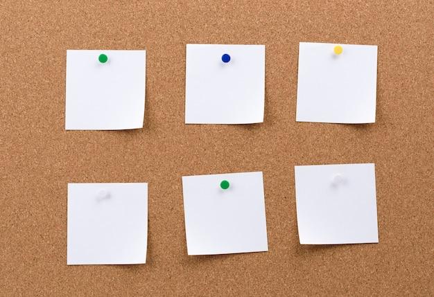 코르크 보드에 고정 된 종이의 흰색 사각형 빈 조각, 복사 공간