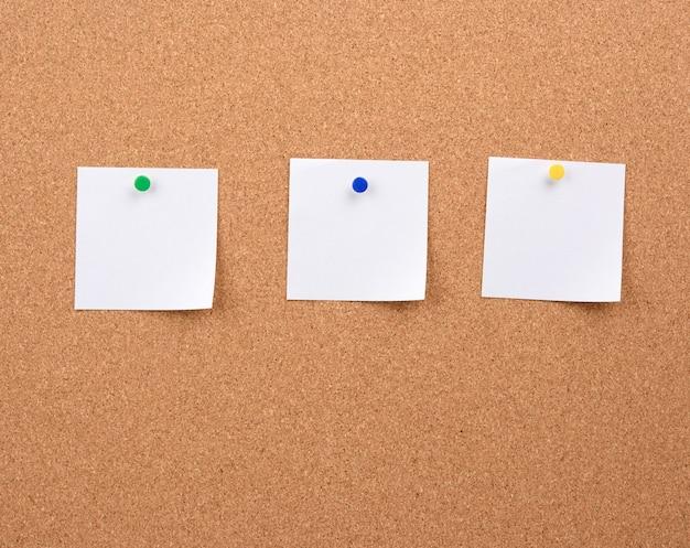 코르크 보드에 고정 된 흰색 사각형 빈 종이 조각,