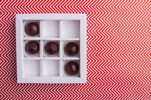 Белая квадратная коробка с круглыми шоколадными конфетами