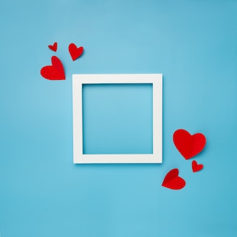 White square frame on blue background with paper hearts