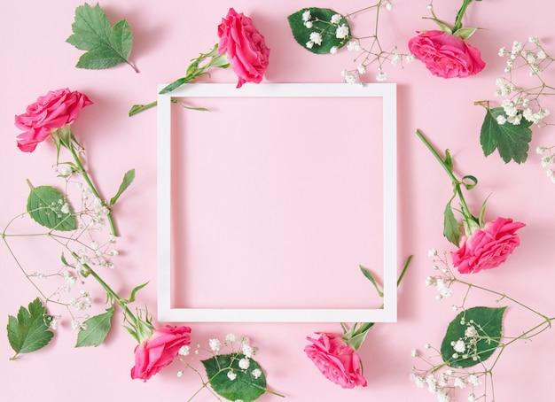 Белая квадратная рамка с розовыми розами на розовом фоне. минималистичная композиция цветочного искусства. копировать пространство