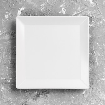 White square plate on grey table . perspective view