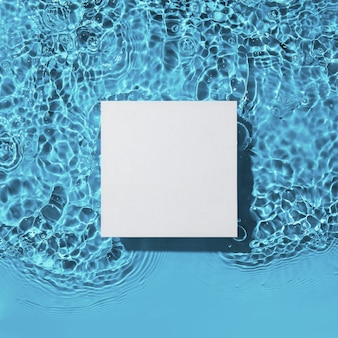 青い水面の背景に白い四角い表彰台フラットレイコピースペース