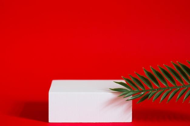 Белый квадратный постамент на красном фоне с зелеными ветвями растений и тенью.
