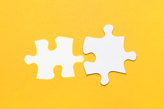 White stamp of puzzle piece with cardboard puzzle piece on yellow surface