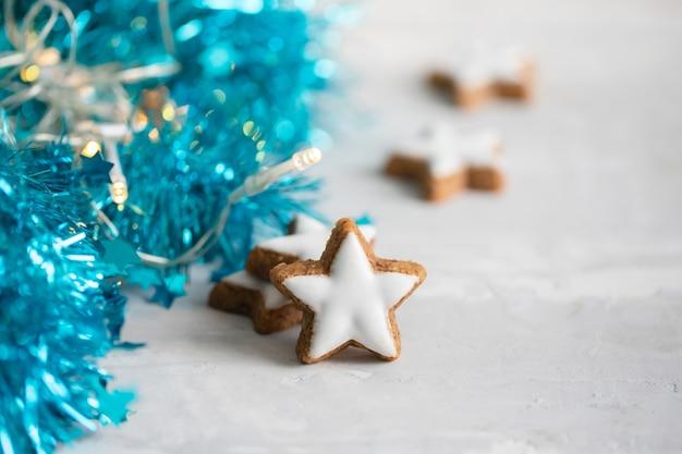 セラミックの背景にクリスマスの装飾が施された白い星のクッキー