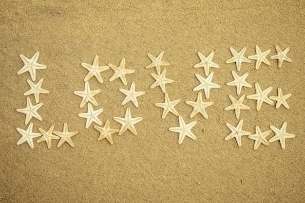 모래에 사랑이라는 단어의 흰색 불가사리 비문. 바다의 별에서 모래 위의 사랑. 휴가 및 여행의 개념입니다.